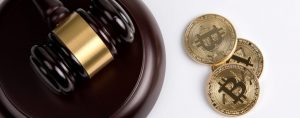 Picture of a gavel and sound block with three bitcoins right next to it